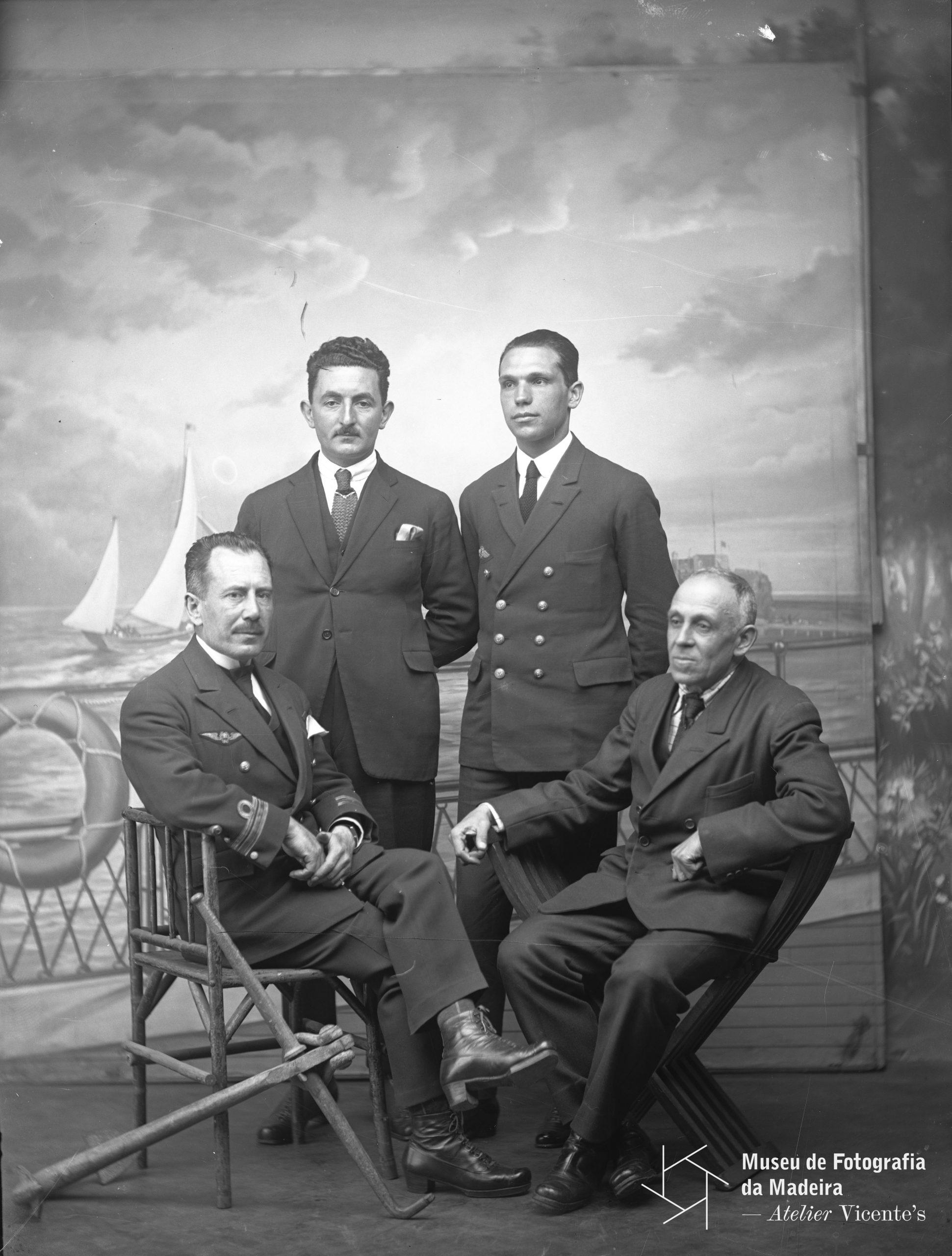 Retrato de grupo com o capitão-tenente Artur de Sacadura Freire Cabral, sentado, à esquerda, e o capitão-de-mar e guerra, Carlos Viegas Gago Coutinho, à direita, acompanhados pelo mecânico Roger Soubiran, de pé, à esquerda, e, à direita, pelo primeiro-tenente, Manuel Ortins Bettencourt, 1921, MFM-AV, em depósito no ABM, Photographia Vicente, Inv. VIC/13253.