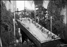 Cadáver de uma mulher num caixão, em local não identificado