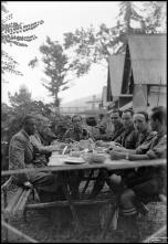Retrato de grupo de oito homens a uma mesa de refeição