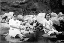 Retrato de uma mulher e uma menina, sentadas numa ribeira