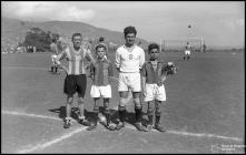 Jogador veterano do União Futebol Clube (atual Clube de Futebol União), dois jogadores infantis e um sénior do Clube de Futebol do Marítimo, no campo dos Barreiros (atual Estádio do Marítimo), durante as comemorações das bodas de prata da Associação de Futebol do Funchal (atual Associação de Futebol da Madeira), Freguesia de São Martinho, Concelho do Funchal