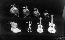 """Quatro barris de diferentes tamanhos, revestidos a vime e com a inscrição """"Madeira"""", um par de botas chãs, uma tenaz de tabaibo e dois cordofones (um uma imitação e outro um braguinha)"""