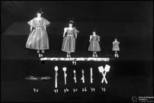 Quatro bonecas de pano, com vestuário regional, uma faixa com motivos regionais e florais, uma faca de madeira com motivos regionais, três colheres de pau, um garfo de pau, uma faca de pau e duas espátulas de pau